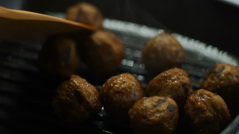 chef fry raw meatballs in iron pan on hot stove for steak dinner meal