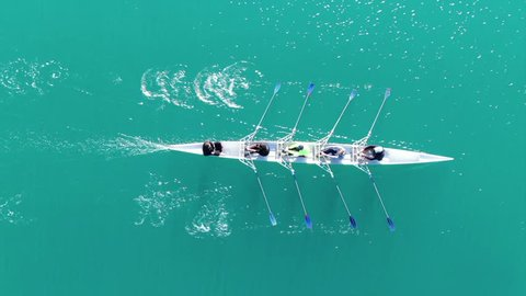 Aerial drone bird's eye view video of sport canoe operated by team of young women in turquoise clear waters