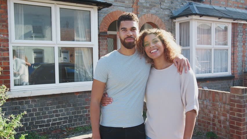 Portrait Of Young Couple Standing Outside New Home In Urban Street | Shutterstock HD Video #1021969411