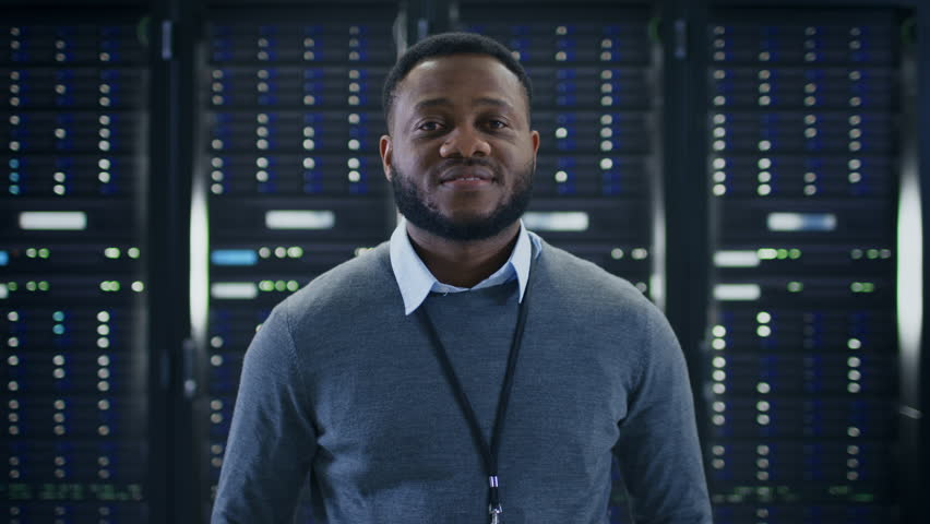Bearded Black IT Engineer Standing and Posing with Crossed Arms in the Middle of a Working Data Center Server Room with Server Computers Working on a Rack. | Shutterstock HD Video #1021974661