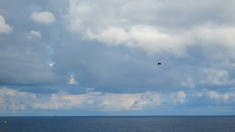 Helicopter heading and landing on an offshore oil rig , service travel to oil and gas platform and drilling rig in offshore locations