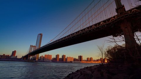 Manhattan bridge with lower Manhattan skyline in the morning with colorful light over East River in New York City