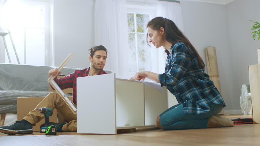 Happy Couple Assembles Furniture as a Team, Girl Reads Instructions and Boy Tightens Screw with a Drill. After Job is Done they do High Five. Moving into New Apartment, Couple Assemble Shelf.