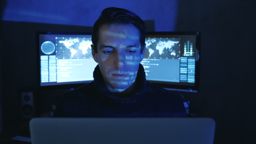 Close-up portrait of a Man Professional IT Programmer in a data center filled with monitor screens. Hacker works at a computer at night in a dark office.   Shutterstock HD Video #1022097361