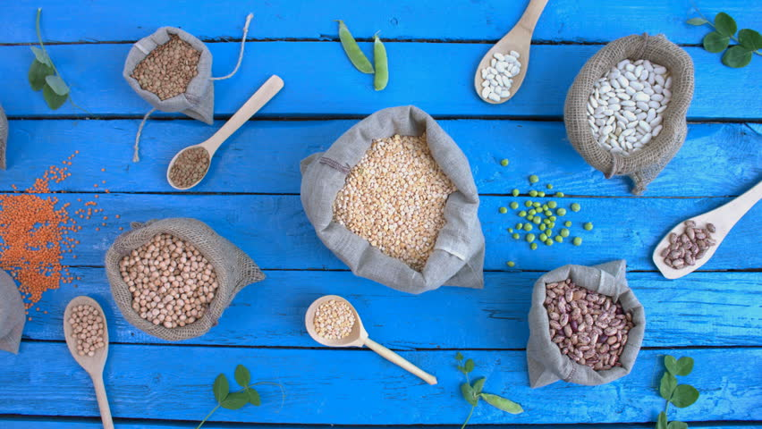 Legumes on wooden ecological background. Beans are located in unusual form on blue wooden table. Bean cultures in woven bags. Camera moves from left to right. | Shutterstock HD Video #1022155801