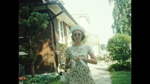 1960s: UNITED STATES: family eat together in garden. Lady walks with girls. Family summer picnic in garden. Girl waves for camera. Couple cook food on barbecue