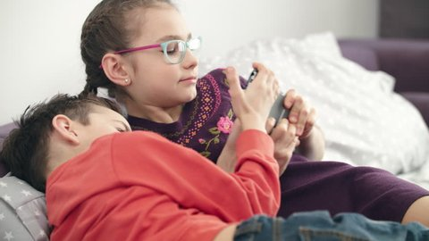 Kids fighting for smartphone at home. Sister and brother can not share mobile phone. Two children argue for gadget at home