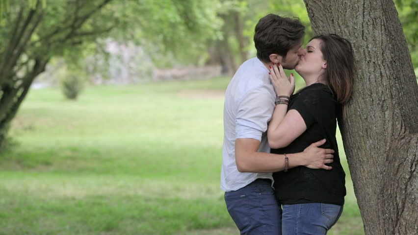 people kissing in the park: two young lovers is having passionate kisses