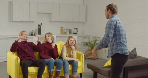 Cheerful man acting out a word in the game of charades, gesturing and showing pantomime to engrossed diverse teenage friends at home. Smart friends guessing word in charades while relaxing indoors.