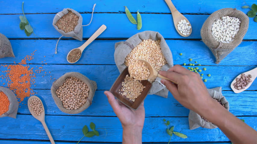 Legumes on wooden ecological background. Beans are located in unusual form on blue wooden table. Hands take peas by spoon from bag to plate. Bean cultures in bags. Camera moves from left to right. | Shutterstock HD Video #1022203021