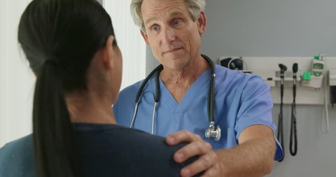 Over the shoulder shot of supportive senior Caucasian male doctor listening to female patient with his hand on her shoulder in hospital exam room. Woman talking to her nurse or OBGYN. Slow Motion 4k