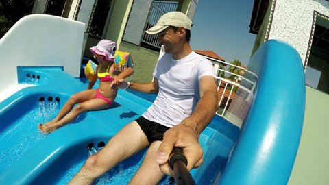 Happy Father and child girl in sliding down the water park ride colorful tube