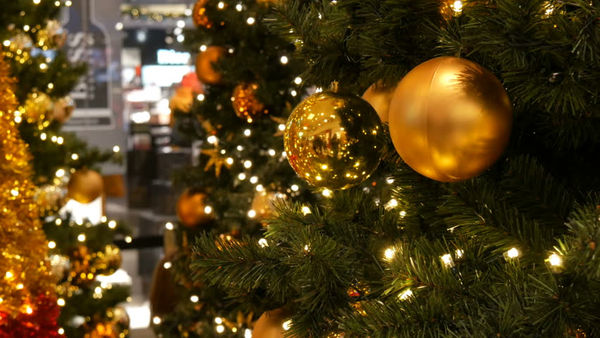 Nuremberg, Germany - December 1, 2018: Beautifully decorated Christmas tree with large gold balls, stars, garlands and artificial snow are in the shopping center in the background strolling shoppers | Shutterstock HD Video #1022262241