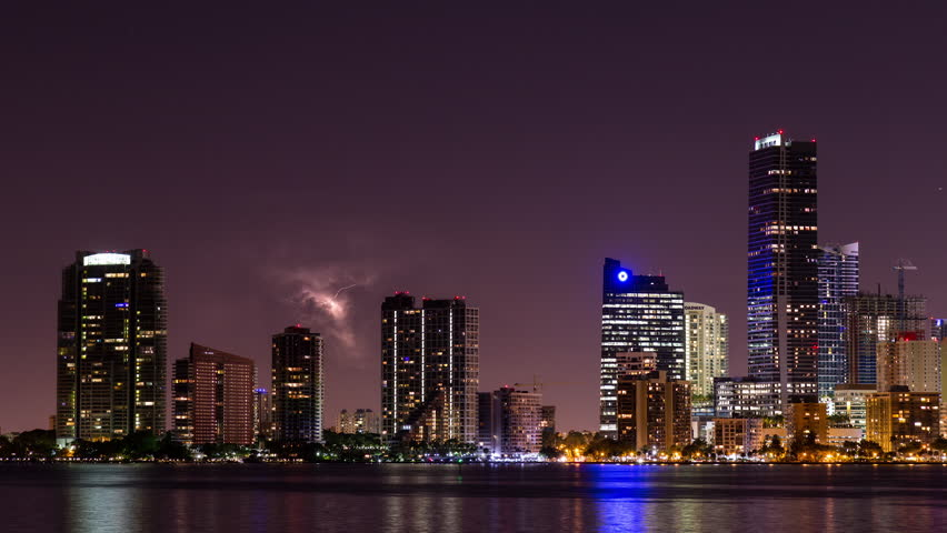 Night timelapse hyperlapse of Miami Brickell and downtown with skyscraper buildings and I-95 Highway Bridge. City skyline illuminated in front of Biscayne bay water. Dead tree branch in foreground