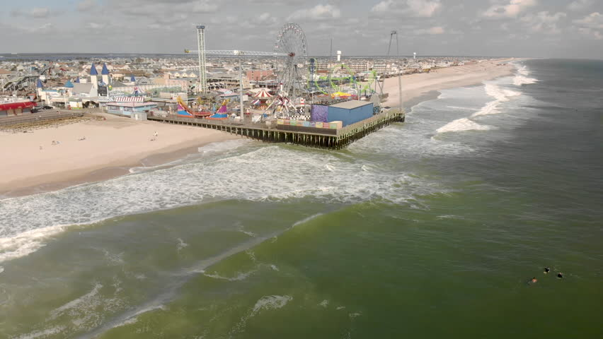 Aerial shot flying above an amusement pier from a sunny beach into the gentle waves of the ocean.