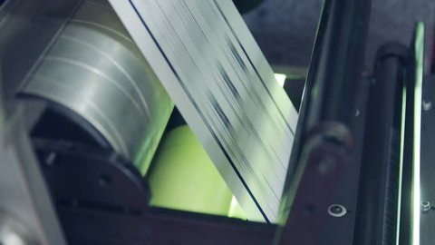 Closeup on paper moving through a large industrial printing machine