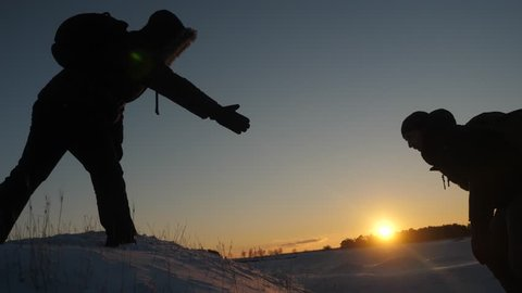 Men help each other to conquer the summit of high snowy mountain by holding hands and stretching each other to top at sunset. Cold natural conditions when traveling. Extreme hikes for brave.