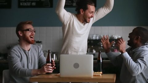 Diverse male friends hangout in pub drink beer watching online football game match at laptop, men fans buddies supporters cheering celebrating victory goal score support winning team, sport betting