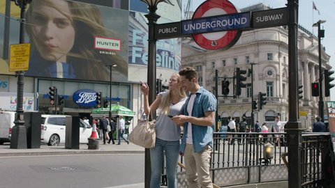 LONDON - JULY, 2018: happy young beautiful tourists by the entrance of underground sign in London. Attractive man and blond woman visiting the city in Piccadilly Circus. Holidays and vacation.