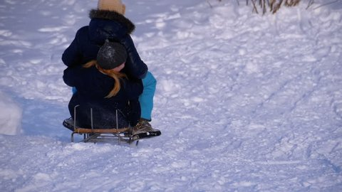 Children Sledding Down a Snowy Hill. Slow Motion in 180 fps. Happy kids move down on a sled. Fun winter holidays. Teenagers children leading down hills, sleigh ride through snow. The descent on a