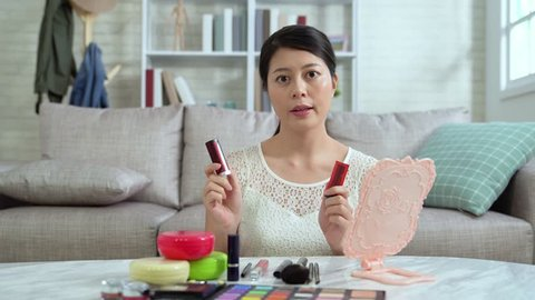 Asian young female blogger recording vlog video with makeup cosmetic at home online influencer on social media concept. famous beautiful vlogger introducing lipsticks in live streaming viral.