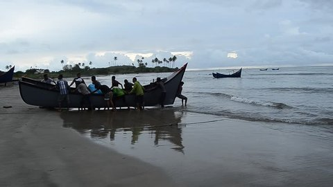 Banda Aceh, Indonesia - November 23, 2016: Community groups push boats on the shore after catching fish, Aceh Besar, Aceh province, Indonesia