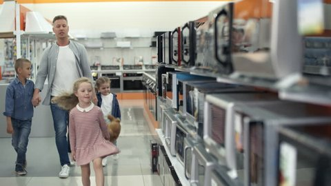 Two little girls and their brother smiling and talking while choosing microwave oven together with dad in home appliance store