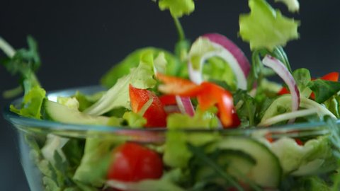 Fresh salad flying to bowl in super slow motion.