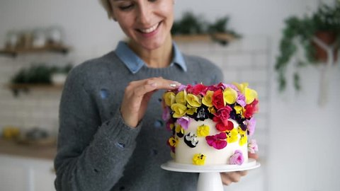 Beautiful, cheerful woman in grey sweater holding self decorated cake with flowers in white modern kitchen studio. Shorthair female chef made a wedding or birthday cake with fresh, eatable flowers