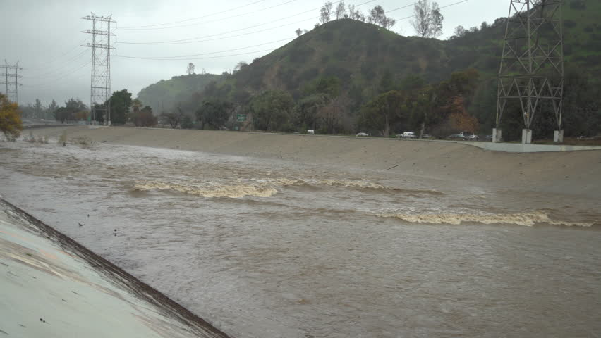 Los Angeles River flows fast after a day of heavy rains in Los Angeles, California.    Shutterstock HD Video #1022577991
