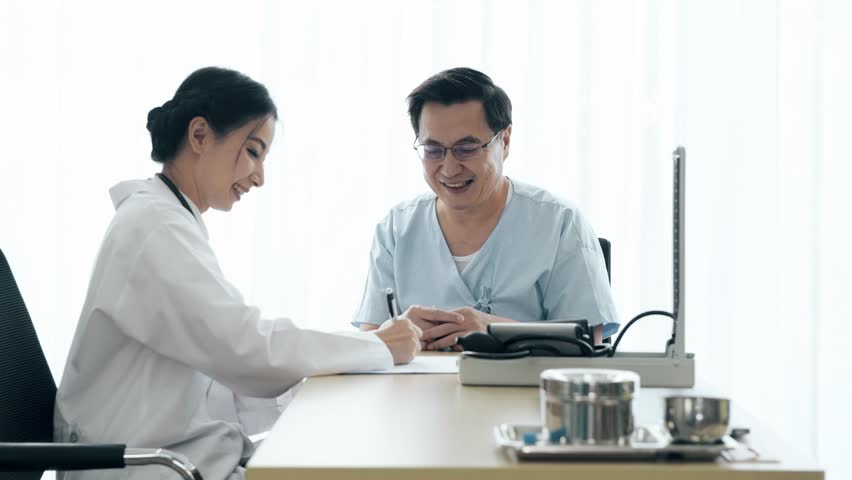 Doctor with patient. Young female medical doctor talking to a senior patient at hospital. Taking notes. Senior care medical and insurance concept. | Shutterstock HD Video #1022583421