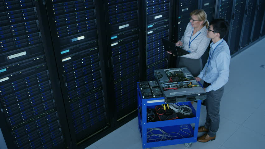 In the Modern Data Center: Engineer and IT Specialist Work with Server Racks, on a Pushcart Equipment for Installing New Hardware. Specialists Doing Maintenance and Diagnostics of the Database.  | Shutterstock HD Video #1022590771