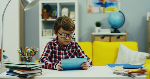 Camera zooming in of the small teen boy in glasses and plaid shirt watching something on the tablet device at the desk in the cozy kid's room.