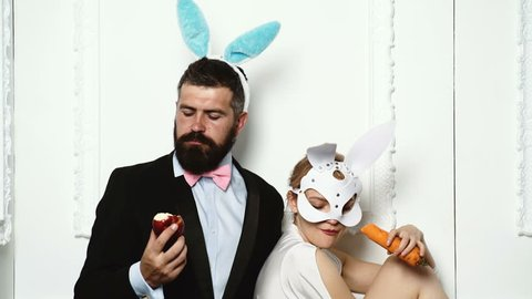 Couple in rabbit costumes with carrots and apple.
