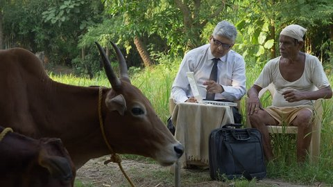 An Executive marketing, explaining scheme to real farmer in India using modern technology like laptop.