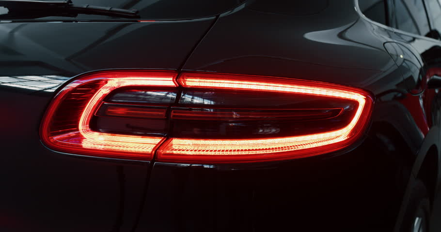 Close up of details of switched on tail lights of anonymous prestigious luxury modern car. Shot in 8K. Concept of passion for driving cars and engines, car dealerships, used cars,luxury cars,auto dial | Shutterstock HD Video #1022658691