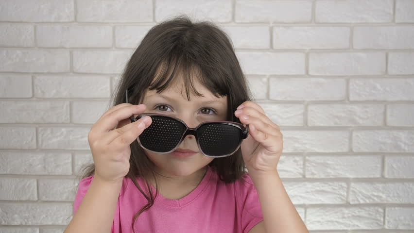 The child puts on glasses for training of sight. Portrait of a child in perforated glasses.