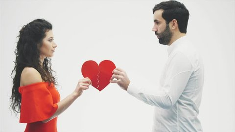 A man and a woman hold two halves of a broken heart on a white background. The concept of gluing the heart. Crisis relationships.