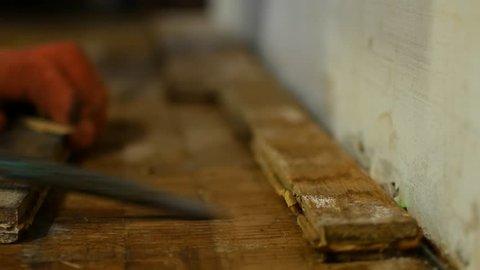The worker dismantles the parquet floor