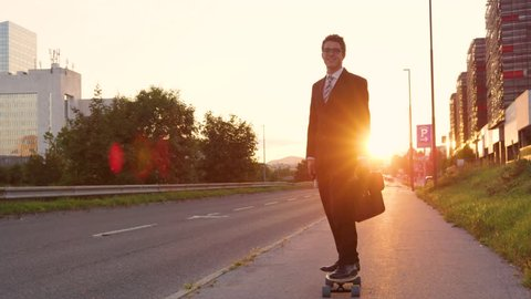 SLOW MOTION, LENS FLARE: Smiling Caucasian businessman skateboarding down the empty sidewalk at sunset. Cheerful yuppie riding his electric longboard cruising home on a picturesque summer evening.