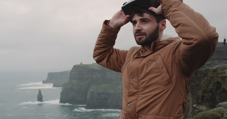 Portrait of a young man playing with a VR on the top of Cliffs with amazing landscape