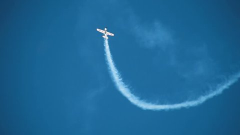Aviation holiday, air show. Pilotage aircraft plane performs aerobatics dizzying stunts in the blue sky over many admired viewers