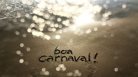 Boa Carnaval message, Portuguese for Happy Carnival, handwritten on sand beach with wave sparkle overlay in Rio de Janeiro, Brazil