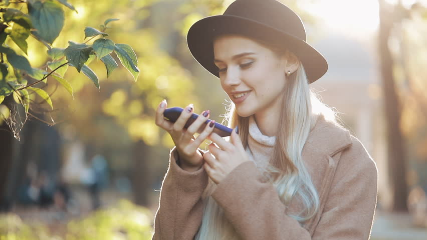 Business lady in black hat sending audio voice message on cellphone at outdoor talking to mobile assistant. Girl using smartphone voice recognition, dictates thoughts, voice dialing message