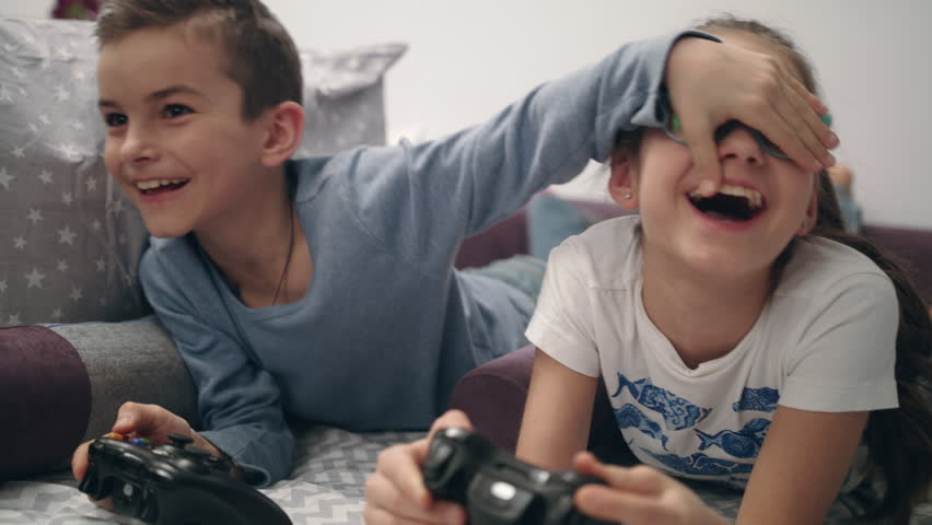 Kids playing video games at home. Brother close eyes sister. Children have fun together with joysticks in hands. Happy siblings enjoy video game