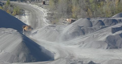 A yellow loaded dump truck rides in a quarry, a working process in a quarry, a stone quarry, a yellow dump truck in a quarry