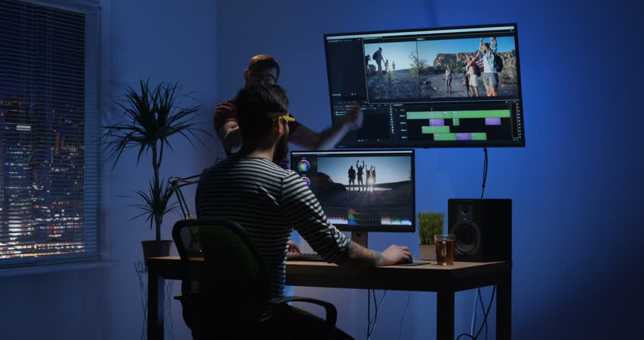 Medium shot of a young man editing video inside the room while his colleague is giving instructions | Shutterstock HD Video #1022891131
