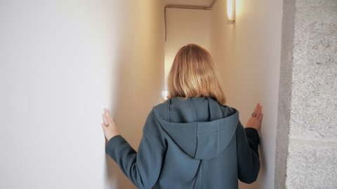 Woman Walking Inside Tight Corridor, Tracking Shot. Tracking shot of a young woman walking through the corridors of an old building. Slow motion