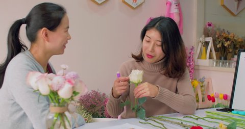 Close up of Asian female florist communication to a client with a flower in hand, teaching explaining to the customer, selling flowers, learning small business, flower lifestyle 4k clip.
