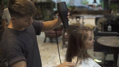 Man hairstylist drying hair of young woman after washing in hairdressing salon. Hairdresser using hair dryer for female hairstyle and cutting in barbershop. Woman hairstyle and beauty